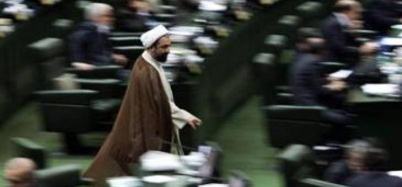 Seorang anggota parlemen berjalan di ruang sidang parlemen Iran