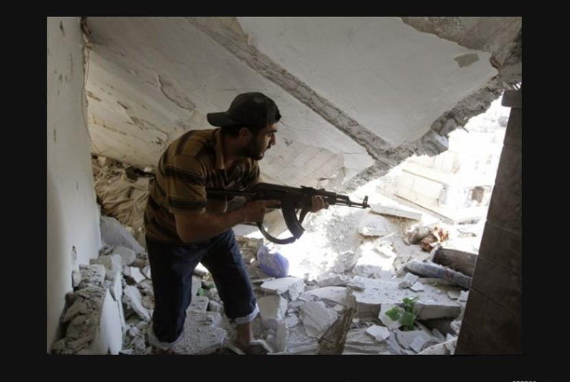 Tentara Pembebasan Suriah menggotong anggotanya yang tertembak saat bentrok dengan militer rezim di Aleppo (Goran Tomasevic/Reuters)