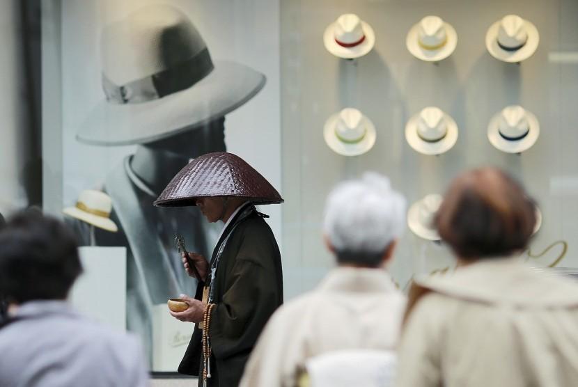 Seorang biksu berdoa di depan jendela  pusat perbelanjaan di Ginza, Tokyo, Jepang. Wisata belanja kini menjadi bagian dari liburan banyak orang.