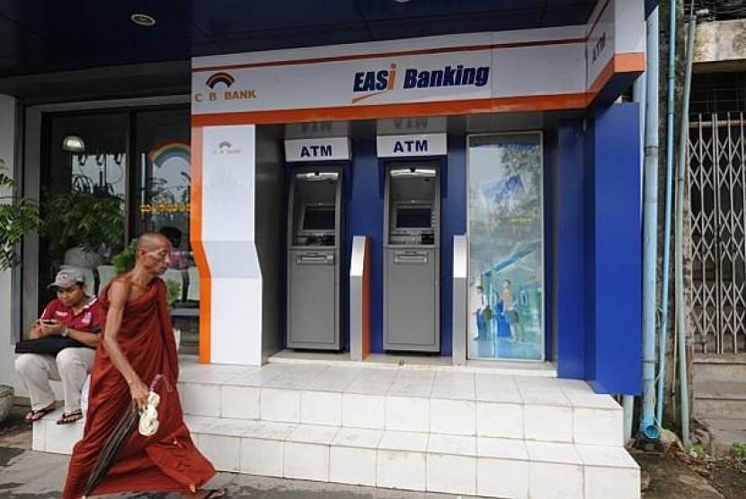 Seorang biksu melintas di depan mesin atm, yang baru saja diperkenalkan demi memfasilitasi pertumbuhan ekonomi dan investasi di negara itu