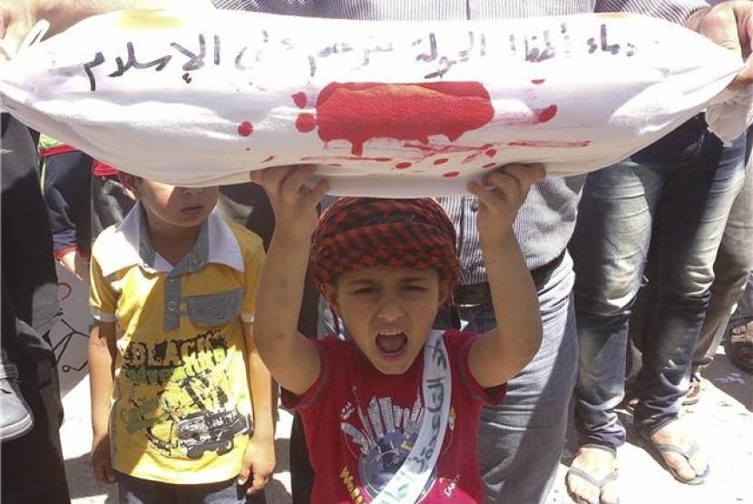 Seorang bocah lelaki memegang sarung guling replika jasad mati saat menggela demonstrasi menentang Presiden Suriah, Bashar al-Assad di Binsh, Idlib, pada Sabtu (1/6)