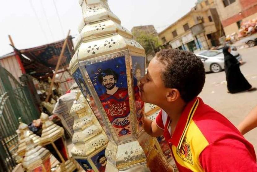 Seorang bocah Mesir mencium lentera hias tradisional yang dikenal dengan nama Fanous bergambar pemain depan sepak bola Mesir, Mohamed Salah.