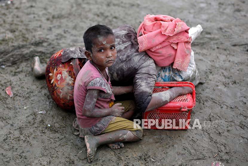 Seorang bocah Rohingya duduk di samping ibunya yang berisitirahat setelah melintasi perbatasan Bangladesh-Myanmar di Teknaf, Rabu (6/9).