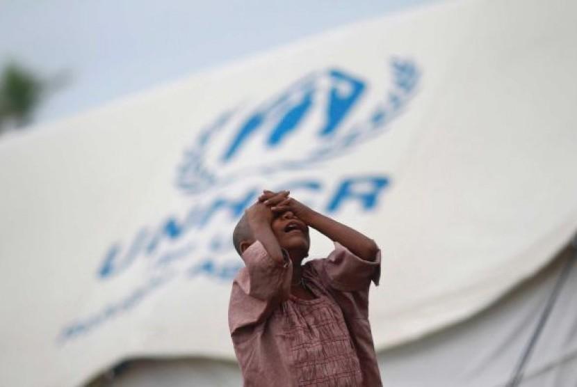 Seorang gadis berdiri di depan sebuah tempat penampungan PBB untuk pengungsi Rohingya yang tinggal di dalam negeri di Myanmar.