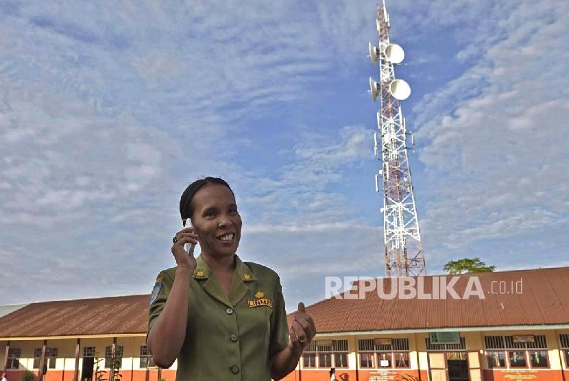 Seorang guru menggunakan layanan jaringan Telkomsel, di Tobelo, Halmahera Utara, belum lama ini.