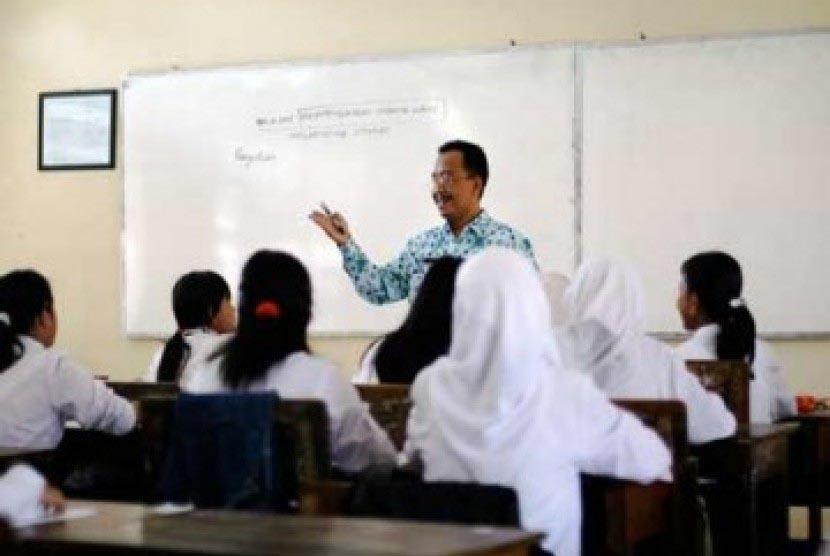 Seorang guru sedang mengajar di kelas.