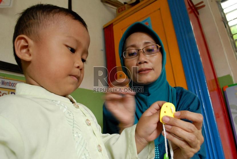 Seorang guru tengah membimbing muridnya di BKB Pendidikan Anak Usia Dini (PAUD) Mawar, Manggarai, Jakarta Selatan, Jakarta Pusat, Kamis (30/8).  ( Republika/Rakhmawaty La'lang)