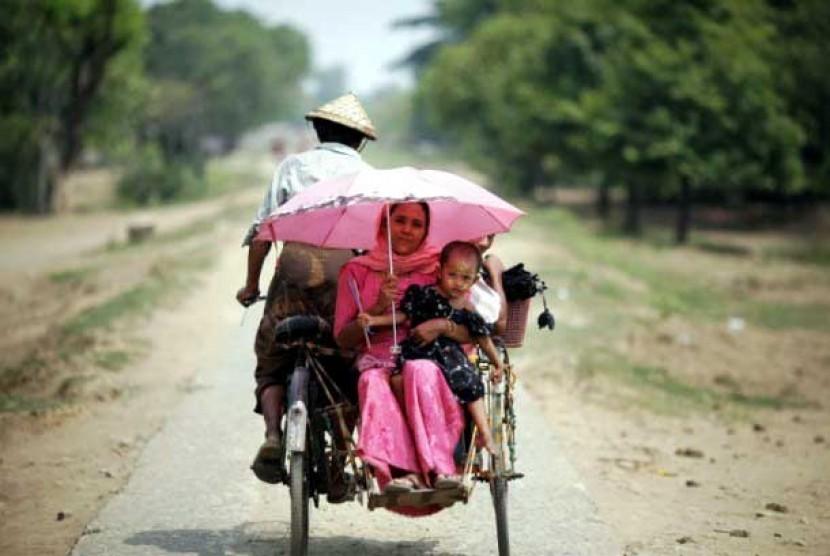 Seorang ibu dari etnis Rohingya beserta anaknya naik becak di sebelah Utara jalan kota Sittwe, Myanmar.