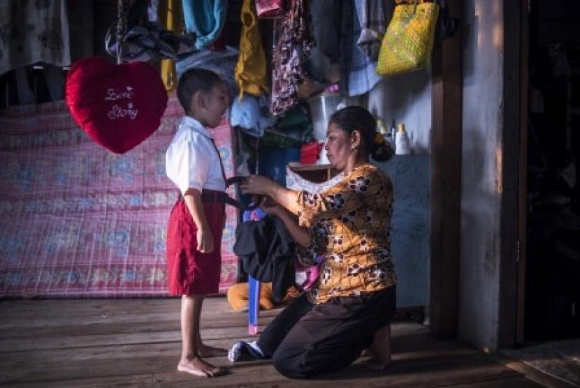 Seorang ibu di daerah terpencil di Kepulauan Karimata, Kalbar memakaikan seragam, Senin (19/10)