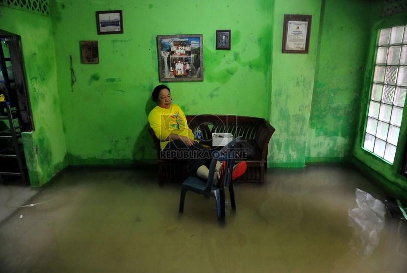 Seorang ibu duduk di dalam rumahnya yang terendam banjir di kawasan pemukiman Kampung Melayu Besar, Jakarta, Rabu (29/1).   (Republika/Prayogi)