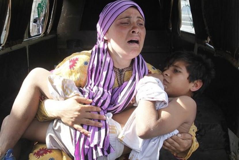 Seorang ibu warga Suriah menggendong anaknya yang jadi korban penembakan di dekat perbatasan Suriah-Lebanon.