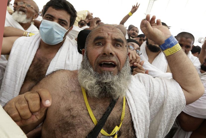 Seorang jamaah haji melempar jumrah, yakni melempar batu pada pilar yang melambangkan setan di Mina dekat kota suci Makkah, Jumat (26/10). (Hassan Ammar/AP)