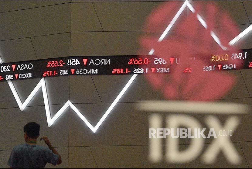 Seorang karyawan melintas di dekat layar pergerakan Indeks Harga Saham Gabungan (IHSG) di Bursa Efek Indonesia, Jakarta, Rabu (7/3). IHSG ditutup melemah 131,84 poin atau 2,03 persen ke level 6.368,27.