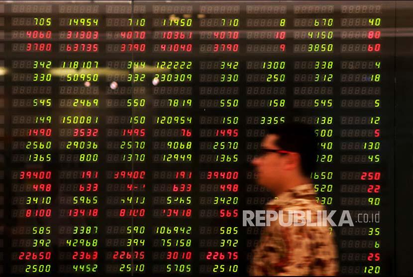 Seorang karyawan melintas di depan monitor pergerakan Indeks Harga Saham Gabungan (IHSG) di Plaza Mandiri, Jakarta, Senin (29/1). Indeks Harga Saham Gabungan (IHSG) pada perdagangan hari ini ditutup menguat 20 poin atau 0,3 persen dibanding penutupan kemarin. IHSG pun kembali mencetak rekor baru di level 6.680, kendati investor asing mencatatkan jual bersih pada perdagangan hari ini.