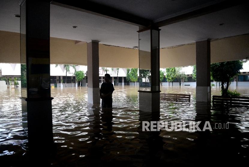 Seorang karyawan melintasi banjir yang menggenagi halaman sekolah SMA Negeri 8 , Bukit Duri, Jakarta, Kamis (16/2).
