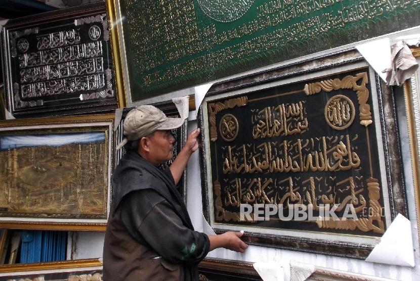 Seorang karyawan toko frame merapihkan display kaligrafi di tokonya di Jakarta, Senin (21/3).