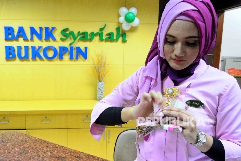 Seorang karyawati tengah menghitung uang di Banking Hall Bank Syariah Bukopin, Jakarta. ilustrasi