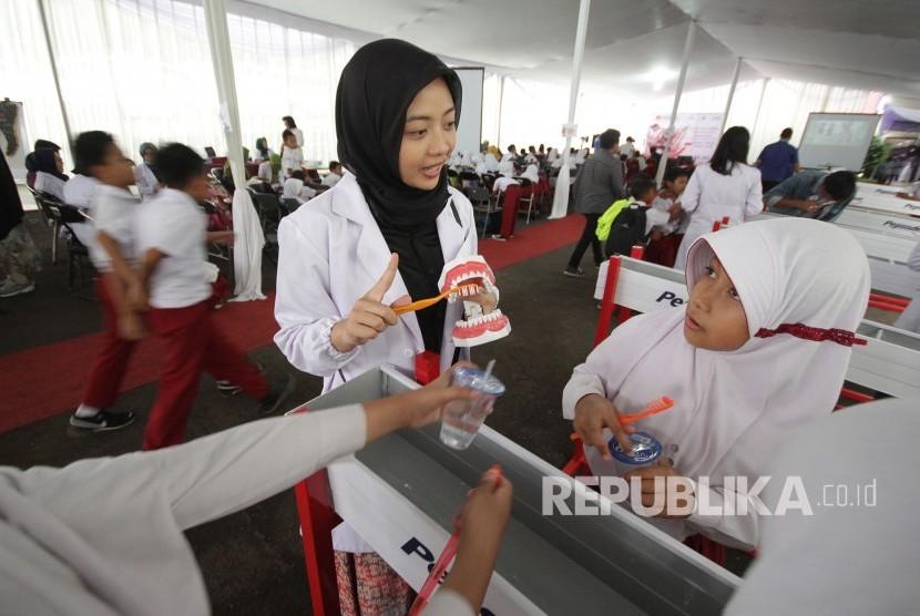 Seorang mahasiswa menjelaskan cara menggosok gigi yang benar pada acara Bulan Kesehatan Gigi Nasional tahun 2017, di FKG Unpad, Jalan Sekeloa Selatan, Kota Bandung, Senin (24/9).