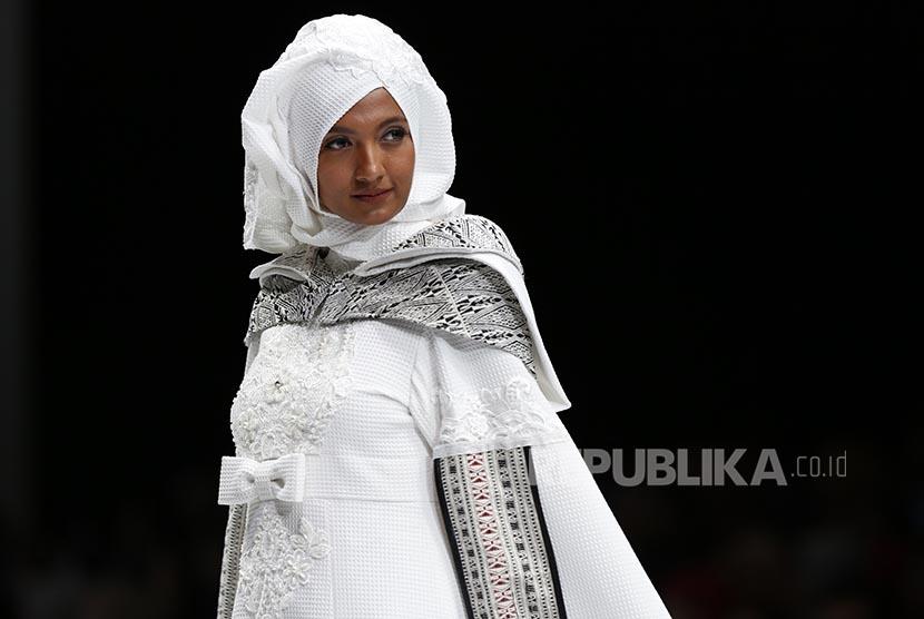 Seorang mode memperagakan pakaian hijab rancangan Jeny Tjahyawati pada acara Indonesai Fashion Week di Jakarta, Rabu (1/2). Setiap 1 Februari diperingati sebagai hari Hijab se-Dunia sejak 2012.