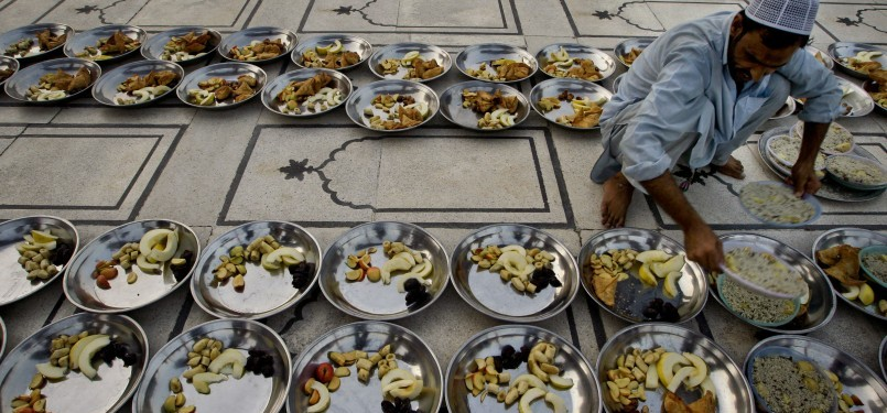 Seorang Muslim Pakistan mempersiapkan tajil berbuka puasa bersama di sebuah masjid di Karachi pada hari pertama Ramadhan. Di Pakistan, Ramadhan hari pertama jatuh pada 2 Agustus.