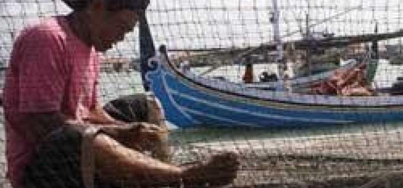 Seorang nelayan sedang mempersiapkan jaring untuk keperluan menangkap ikan.