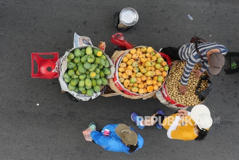 [Ilustrasi] Seorang pedagang buah melayani konsumennya.