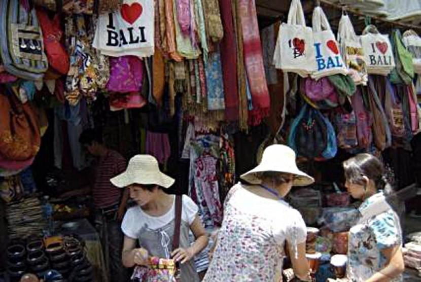 Seorang pedagang melayani wisatawan asing saat mereka berbelanja di Pasar Seni Ubud, Bali, Jumat (16/10).