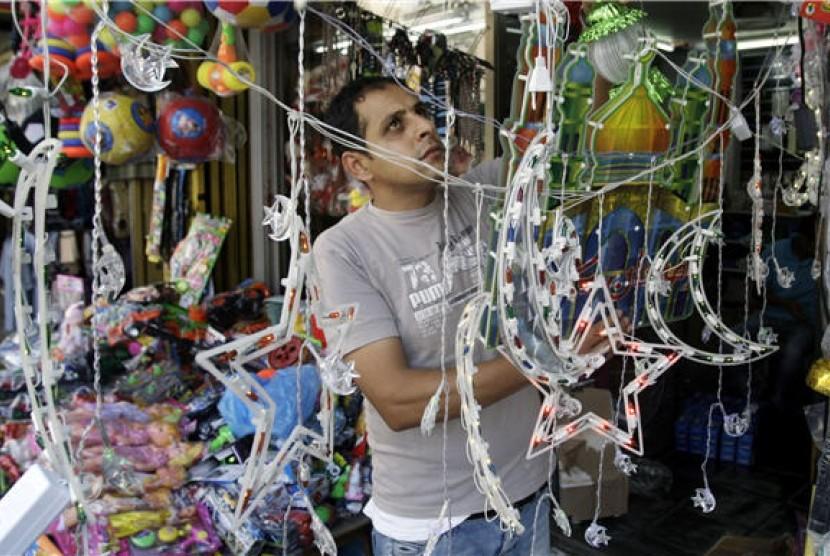 Seorang pedagang Palestina merapihkan barang dagangannya berupa pernak-pernik dekorasi Ramadhan.