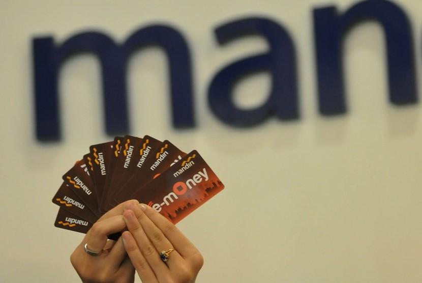 Seorang pegawai menunjukkan model layanan uang elektronik (E-Money) berbentuk kartu dari Bank Mandiri, di Jakarta, Selasa (51/7).  (Republika/Prayogi).