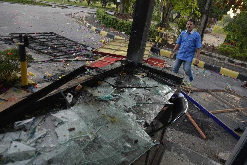 Seorang pegawai Rektorat Universitas Riau melintasi pos keamanan yang rusak parah akibat bentrokan di Gedung Fakultas Ilmu Sosial dan Politik Universitas Riau, di Kota Pekanbaru, Jumat (6/10).