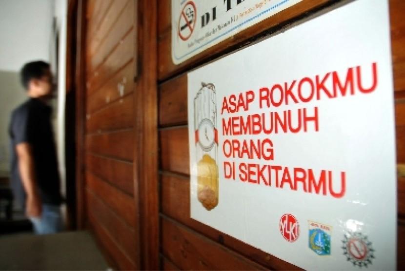 Seorang pekerja melintas disamping poster larangan merokok (ilustrasi)