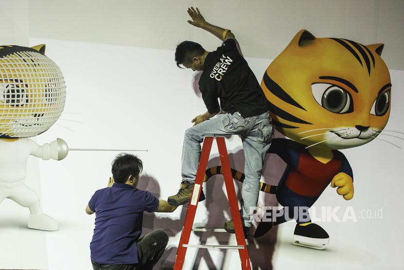 Seorang pekerja menyiapkan papan reklame SEA Games 2017 di media center di Kuala Lumpur, Malaysia, Jumat (11/8).