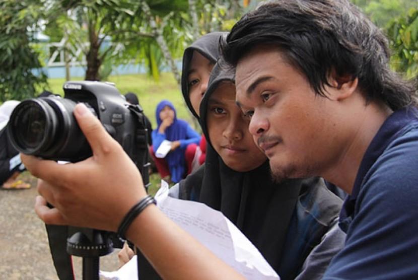 Seorang pelajar serius menyaksikan penggunaan kamera untuk pembuatan film