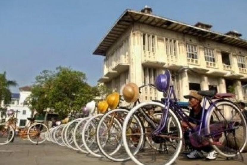 Seorang pemilik persewaan sepeda onthel merapikan deretan sepedanya di Kompleks Kota Tua, Jakarta.