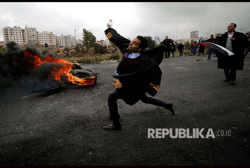 warga Palestina melemparkan batu ke arah militer Israel.