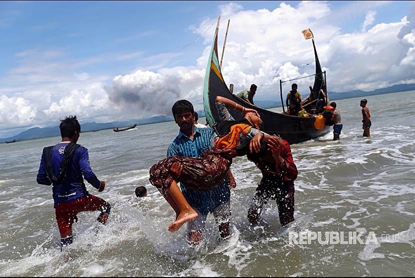 A Rohingya refugee was carried into the waters of the Bay of Bengal while smoke billowed from a distance of Myanmar, in Shah Porir Dwip, Bangladesh, Tuesday (September 11).