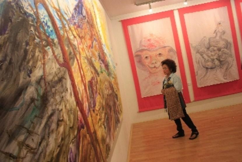 Seorang pengunjung sedang mengamati pameran karya keluarga sang maestro Afandi di galeri Nort Art Space (NAS), Pasar Seni, Jakarta, Jumat, (20/4). Pameran yang diselenggarakandari tanggal (20/4) sampai (25/5) mendatang ini merupakan karya keluarga dari Aff