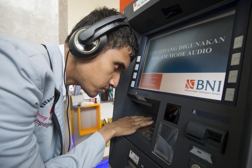 Seorang penyandang disabilitas mencoba bertransaksi di mesin ATM Bank BNI yang dilengkapi fasilitas bagi penyandang disabilitas. ilustrasi