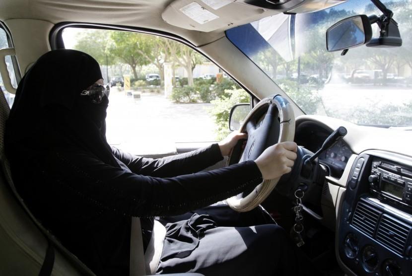 Seorang perempuan Arab Saudi mengemudikan kendaraan di Riyadh, Arab Saudi pada 28 Oktober 2013. Berdasarkan laporan pada Selasa (26/9) waktu serempat, Raja Saudi Salman bin  Abdulaziz Al Saud mengeluarkan dekrit yang mengizinkan perempuan mengendarai kendaraan. Dekrit ini berlaku mulai Juni 2018.