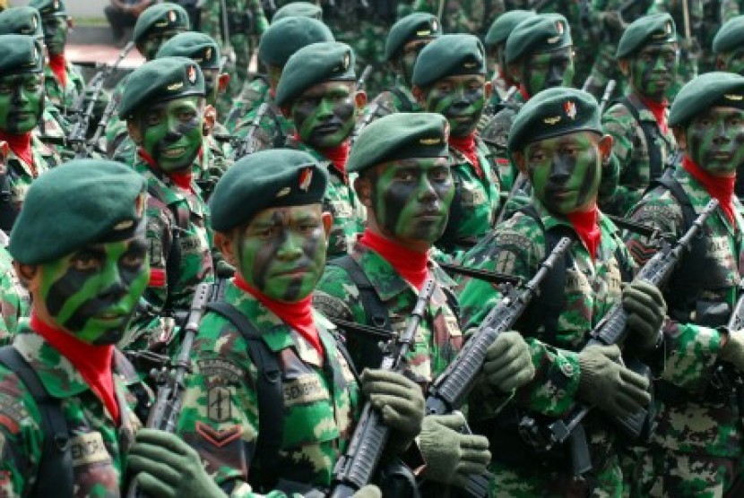 Seorang personil TNI AD menjelaskan peralatan persenjataan kepada sejumlah siswa saat sebuah pameran Alat Utama Sistem Persenjataan (Alutsista) TNI.