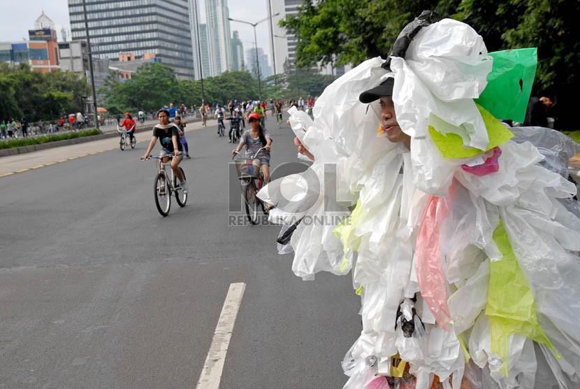 Seorang peserta kampanye memberikan sosialisasi pengurangan sampah kantong plastik kepada warga yang melintas di Jalan Jenderal Sudirman, Jakarta, Ahad (24/2).  (Republika/Agung Fatma Putra)