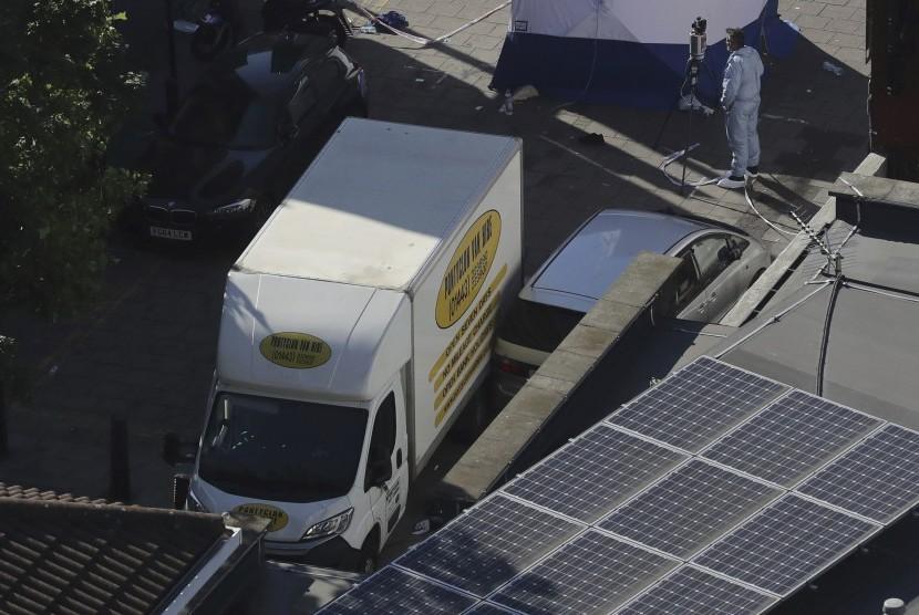 Seorang petugas forensik sedang memeriksa sebuah mobil van di dekat stasiun Finsbury Park setelah kendaraan tersebut menghantam pejalan kaki di London utara, Senin (19/6).