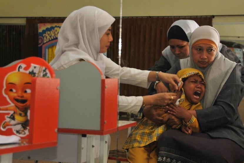 Seorang petugas kesehatan memberikan vaksin Difteri di PAUD Yasmin Fakultas Keguruan Dan Ilmu Pendidikan Universitas Muhammadiyah Jember, Jawa Timur.