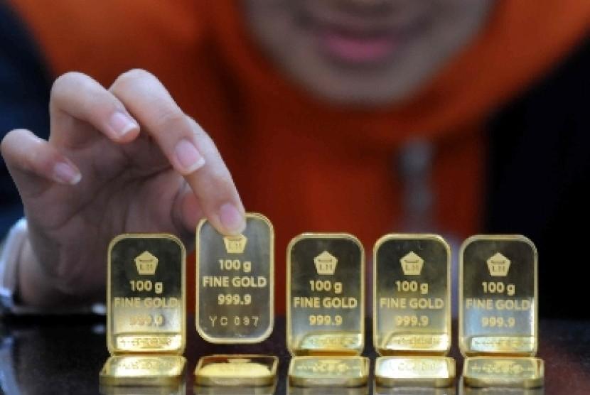 Seorang petugas menunjukkan emas batangan di salah satu outlet bank syariah.
