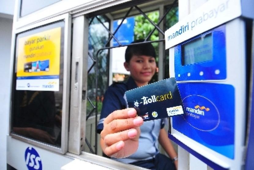 Seorang petugas parkir ISS Parking Management menunjukkan kartu e-toll Mandiri yang dapat digunakan untuk pembayaran biaya parkir dengan parkir ISS Parking di Jakarta.