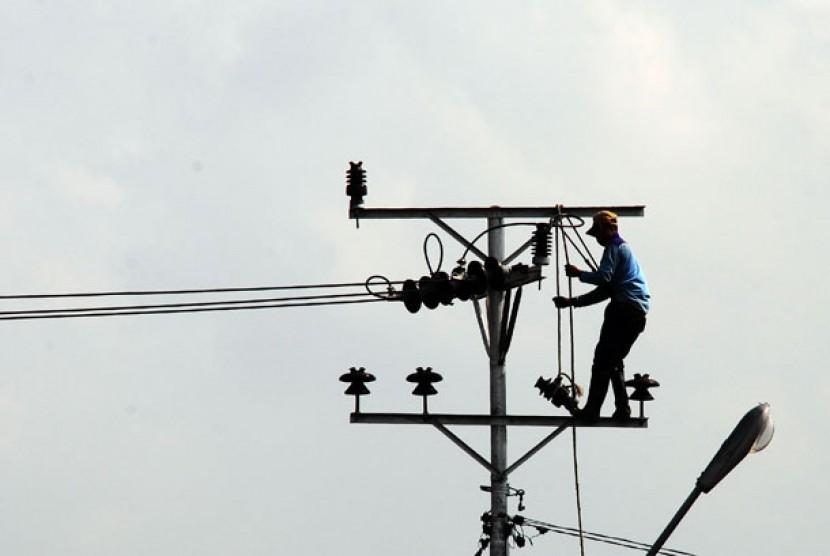 Seorang petugas PLN melakukan perbaikan instalasi jaringan listrik.