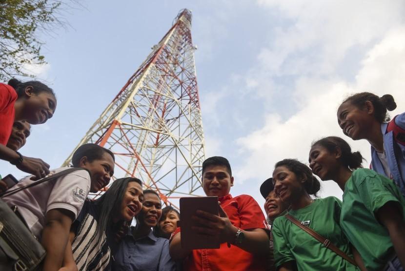 Seorang petugas Telkomsel bersama pemudi Alor mencoba layanan data pada selular di dekat base transceiver station (BTS),