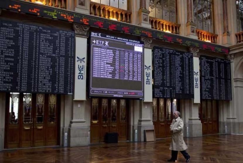 Seorang pialang melintas di depan layar saham di Bursa Efek Madrid, Spanyol.