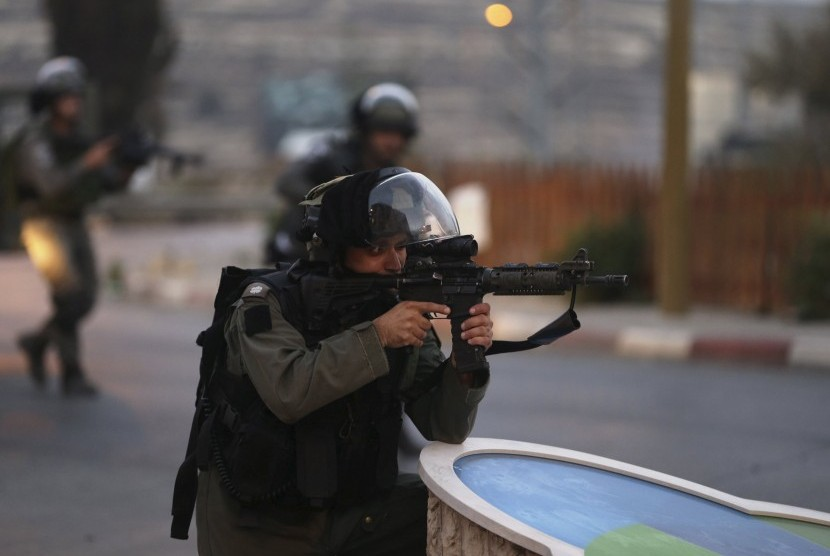 Seorang polisi perbatasan Israel membidik senjatanya selama bentrokan dengan warga Palestina di dekat pemukiman Yahudi Bet El, dekat kota Tepi Barat yang diduduki Ramallah.