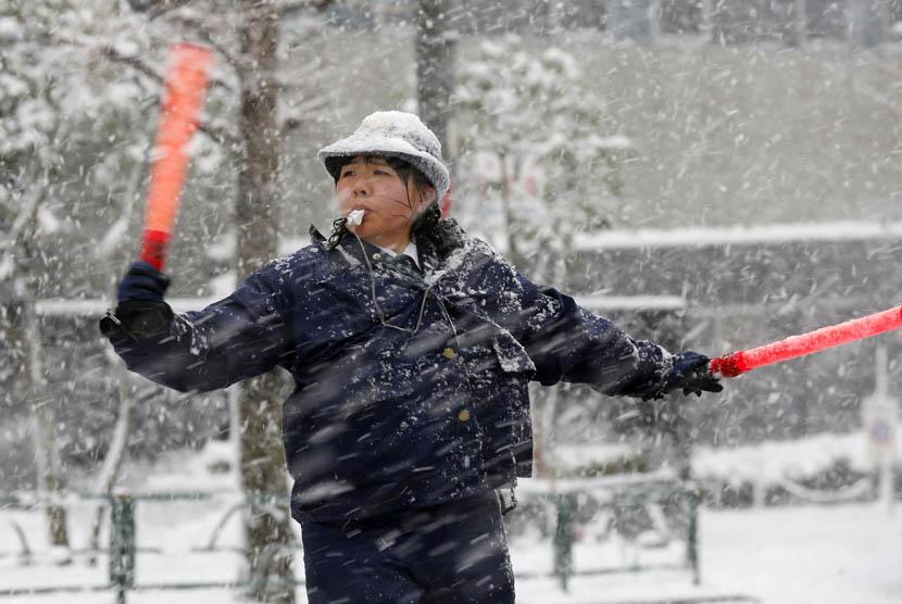 Seorang polisi wanita mengatur lalu lintas saat hujan salju di Tokyo